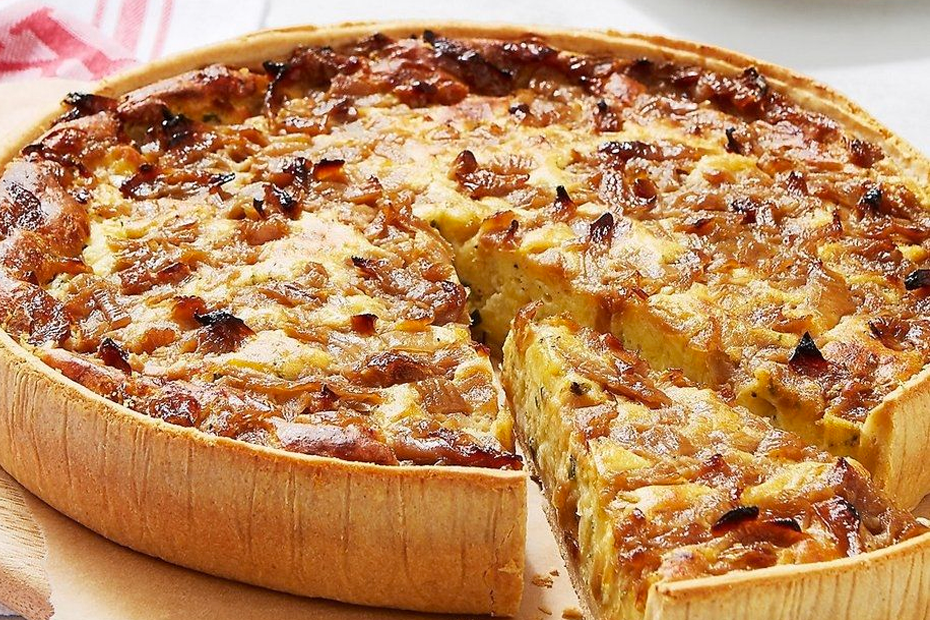 A quiche on a plate with a slice cut out